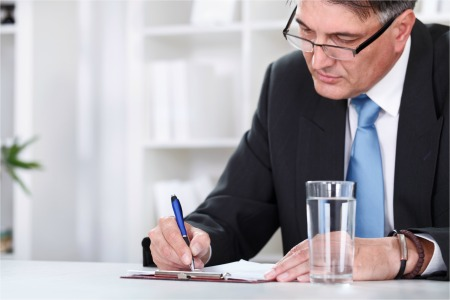 Businessman with document, signing a contract with pen